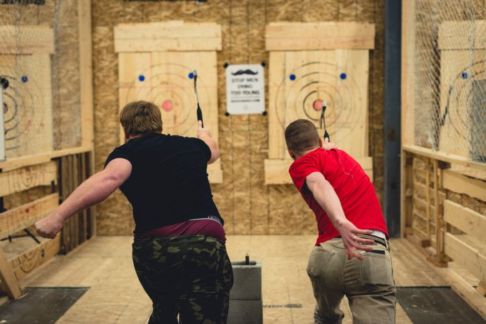 Two guys throwing axes in surrey
