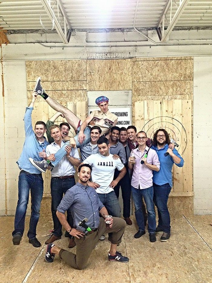 Group shot of bachelor party holding up the groom at Bad Axe Throwing Toronto