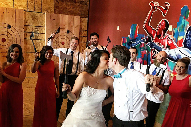 Bride and Groom kiss while holding axes at Bad Axe Throwing Chicago